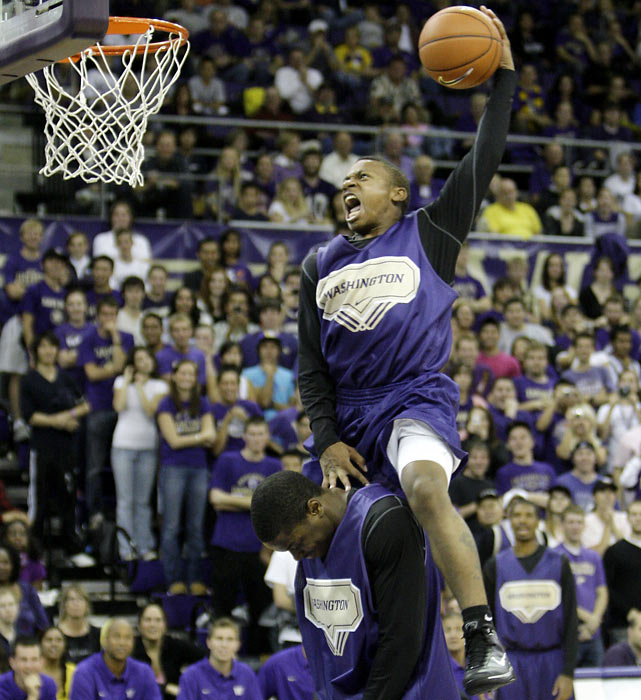 Washington's Isaiah Thomas uses teammate Matthew Bryan-Amaning as a boost during a dunk contest at the Huskies' 2009 Midnight Madness.