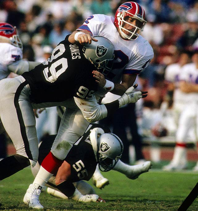 Raiders' defensive tackle Sean Jones torpedoes Buffalo quarterback Jim Kelly during their Dec. 6 contest in Los Angeles Memorial Coliseum.  Though Kelly led the Bills' to four Super Bowl appearances, he was not as successful in 1987, guiding his team to a pedestrian 7-8 record.  The Raiders won this game 34-21.