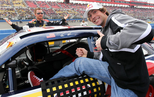 Pastrana throws the thumbs-ups as he stands near fellow Red Bull racer Brian Vickers stock car.