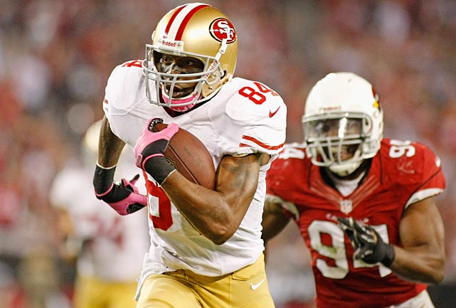 Randy Moss, pictured here running away from an Arizona Cardinals defender, joined the Niners in 2012, primarily as a third wide receiver option behind Michael Crabtree and Mario Manningham. He caught 28 passes for 434 yards in the regular season with three touchdowns.
