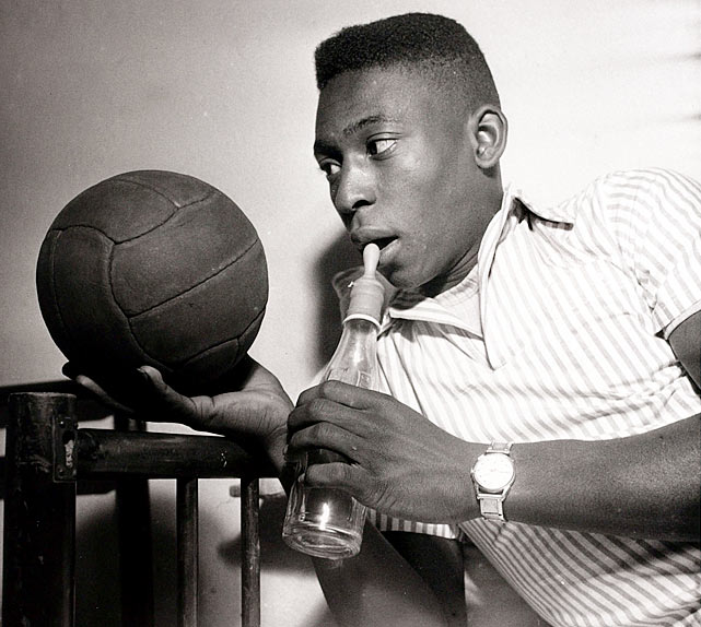 A young Pele prepares to drink from a bottle topped by a teat.  He was prolific even in his youth, spearheading the 1958 Brazil National Team to a World Cup championship over Sweden at age 17.
