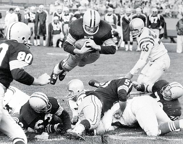 Green Bay great Paul Hornung springs over a pack of defenders.