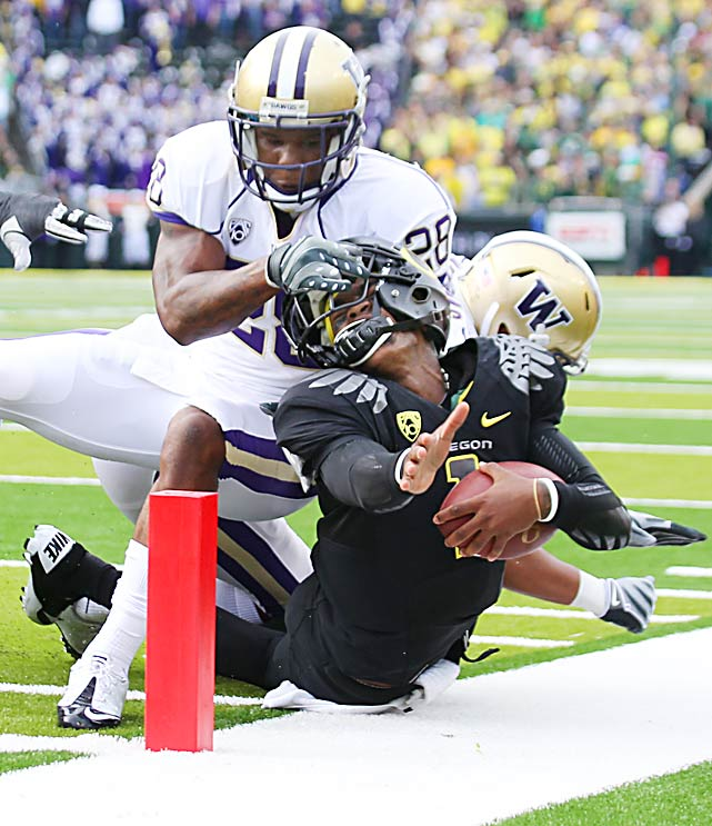 Cornerback Quinton Richardson of Washington twists the helmet of Oregon quarterback Darron Thomas as Thomas made a dash for the end zone during the second quarter of Oregon's 53-16 victory. Thomas was down at the one-yard-line and the face mask penalty was called.