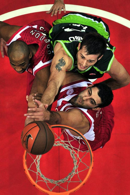 Unicaja's Joel Freeland scores over Olympiakos' Ioannis Bourousis and Jamon Lucas during their Euroleague basketball game Nov. 3 in Athens.  Olympiakos defeated Unicaja 93-66.