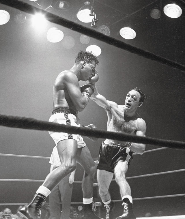 Basilio ( right ) outpointed Sugar Ray Robinson for the title at Yankee Stadium, despite giving away considerable height and reach advantages, in one of the most action-packed bouts of all-time.