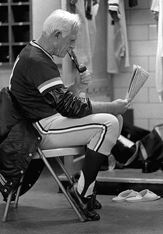 Anderson relaxes with a pipe and newspaper in the Tigers locker room before a game against Milwaukee. Anderson is the only manager to win World Series titles in both leagues.