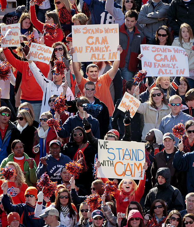 Fans at Jordan-Hare Stadium hold up signs of support for Newton.