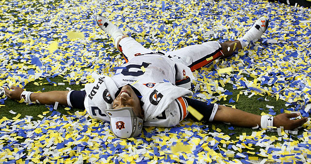 Newton makes snow angels in the confetti after Auburn's victory over South Carolina. The victory secured a spot in the BCS National Championship game on Jan. 10 against Oregon.
