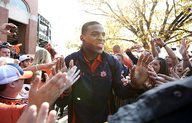 Though some fans and coaches thought Newton should sit amidst the allegations, the quarterback continued to play. In this photo, he is greeted by Tiger fans before Auburn's game against Georgia on Nov. 13. Newton would throw for two touchdowns and run for another two in the Tigers' 49-31 victory.
