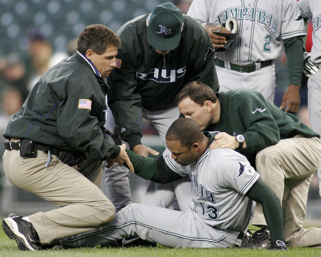 Crawford is helped to his feet by the Rays' trainers and manager Lou Piniella after bruising his left knee while sliding into first base.