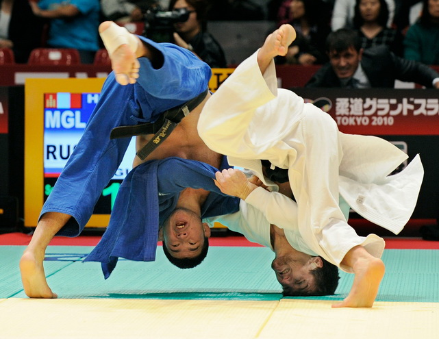 Musa Mogushkov (in white) of Russia throws Tsagaanbaatar Hashbaatar of Mongolia during their men's 66kg class semifinal match in the Judo Grand Slam Tokyo judo tournament in Tokyo. Mogushkov defeated Hashbaatar.