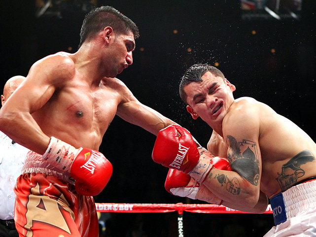 Amir Khan connects with a left to the face of Marcos Maidana during their WBA super lightweight title fight at Mandalay Bay Events Center in Las Vegas on Dec. 11. Khan won by unanimous decision to keep his 140-pound WBA title.