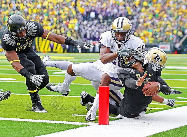 Washington Huskies cornerback Quinton Richardson nearly rips Oregon Ducks quarterback Darron Thomas' head off as the latter dashes for the goal line during the second quarter of Oregon's 53-16 victory.
