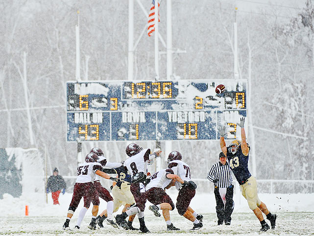 Augsburg College quarterback Muneer Al-hameed (8) throws a pass over Bethel University defender Trent Pearson as snow blankets the field in Arden Hills, Minn.  Bethel would defeat its rival 19-6 to earn a berth in the first round of the Division III playoffs.