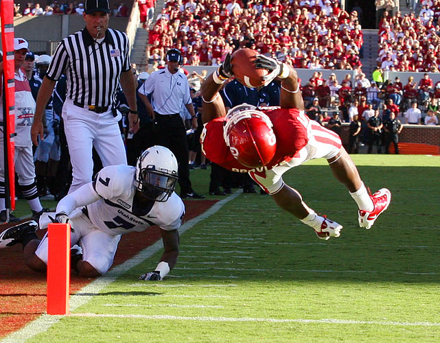 Oklahoma wide receiver Ryan Broyles leaps over the goal line after eluding Utah State cornerback Chris Randle during the Sooners' 31-24 win over the Aggies in Norman, Okla.