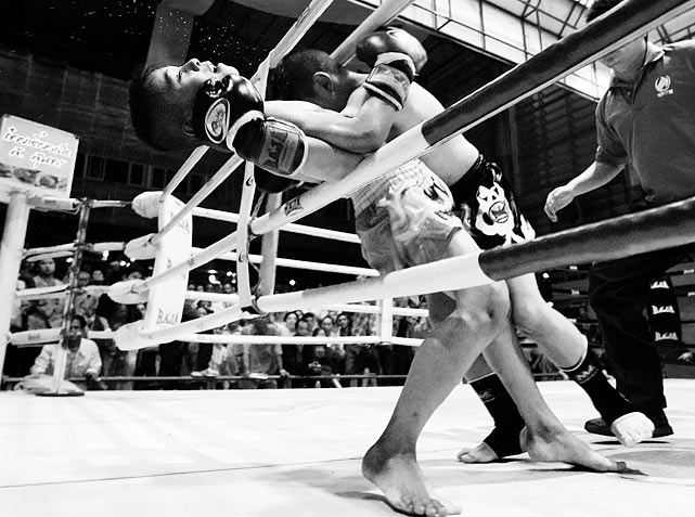 A bout between two children spills out of the ring at the Thai Boxing School for Kids in Nakhon Ratchasima, Thailand.