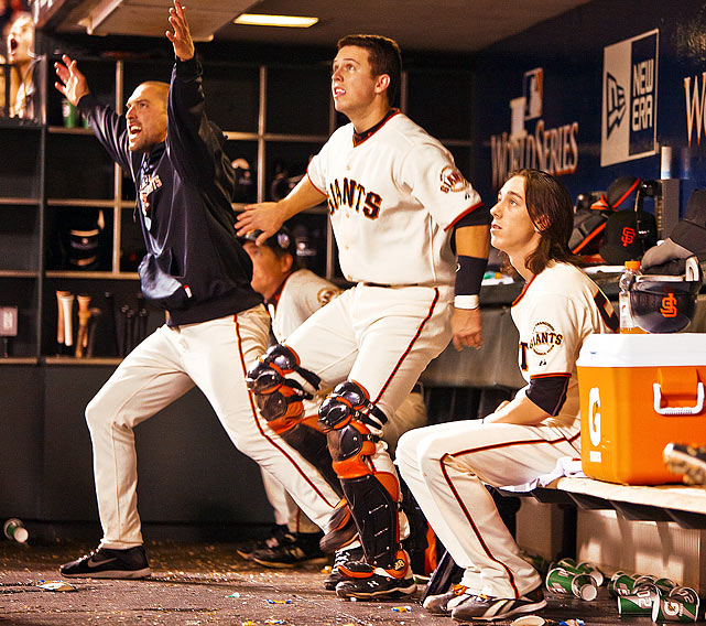 San Francisco Giants catcher Buster Posey (center), left fielder Mark Derosa (left) and pitcher Tim Lincecum (right) watch from the dugout as teammate Juan Uribe homers during the Giants' 11-7 victory in Game 1 of the World Series at AT&T Park in San Francisco.