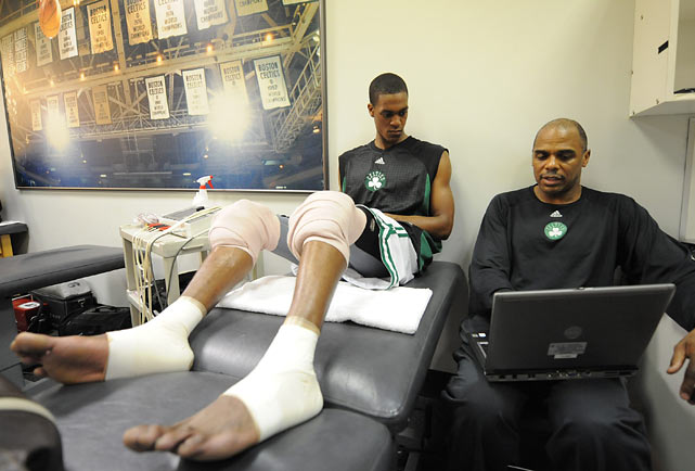 Rondo looks over plays with assistant coach Armond Hill before a game.