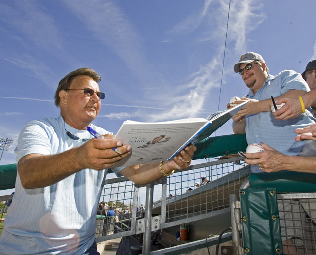 Santo signs some autographs before a spring training game in Mesa, Ariz.
