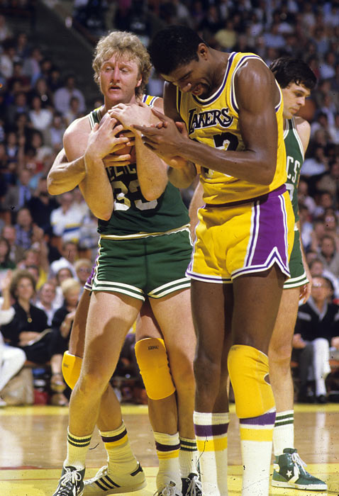 Larry Bird controls possession of the basketball as Magic Johnson claps during Game 3 of the 1984 NBA Finals.