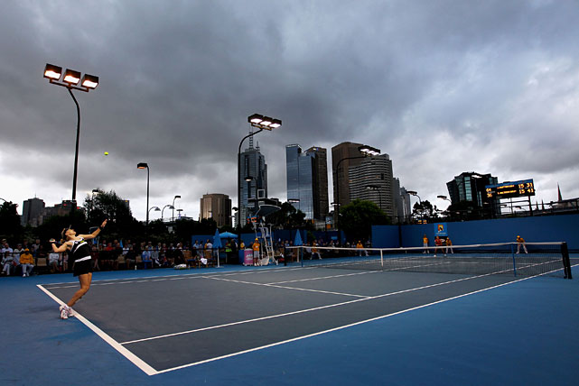 Great Britain's Elena Baltacha serves as clouds loom over the outer courts during her first-round match against Jamie Hampton of the United States.