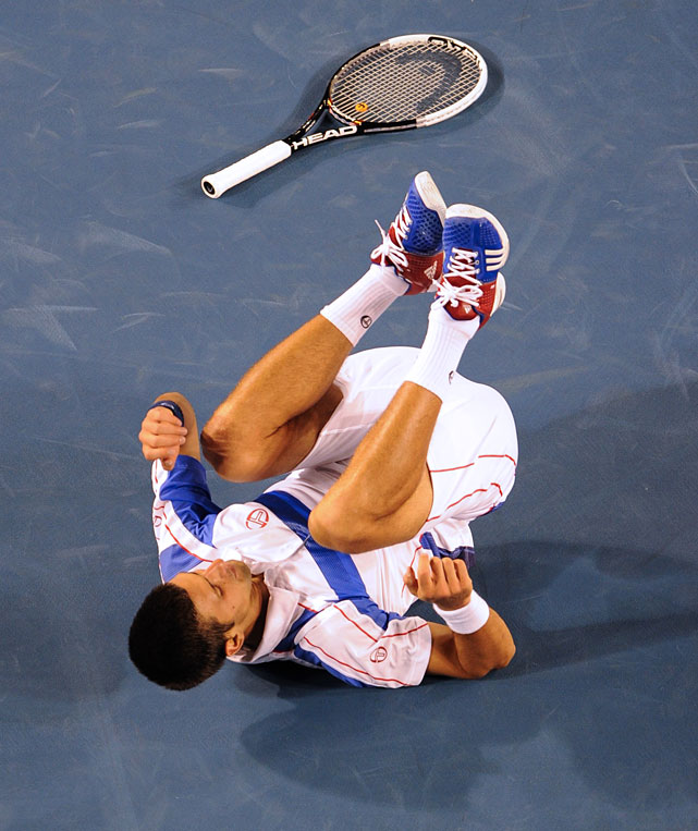 Djokovic recovers from a fall during his match against Federer.