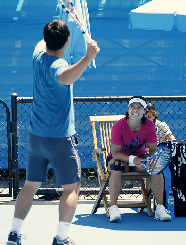 Li (right) watches as her husband and coach Jiang Shan (left) gives her advice during a practice session on Friday.