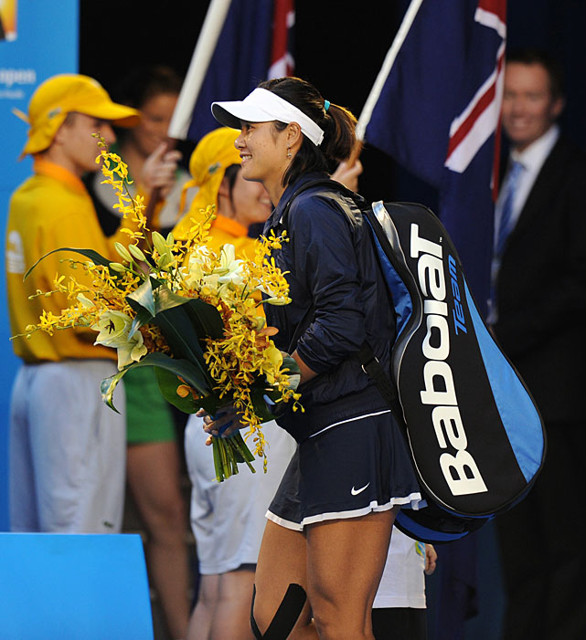Li carries a bouquet of flowers as she enters the court for Saturday's final.