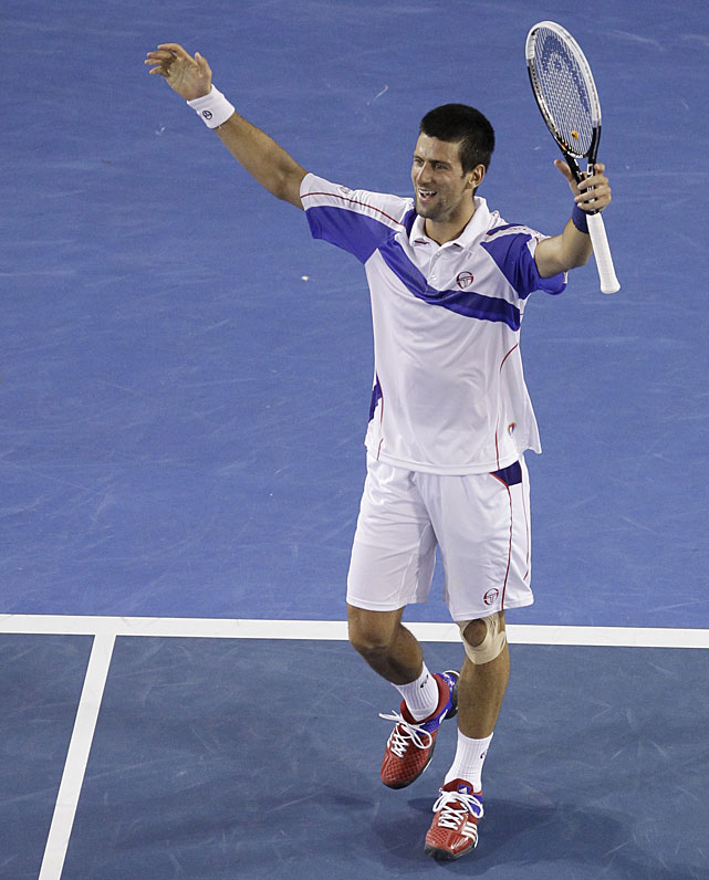 Djokovic raises his arms in celebration after the victory.
