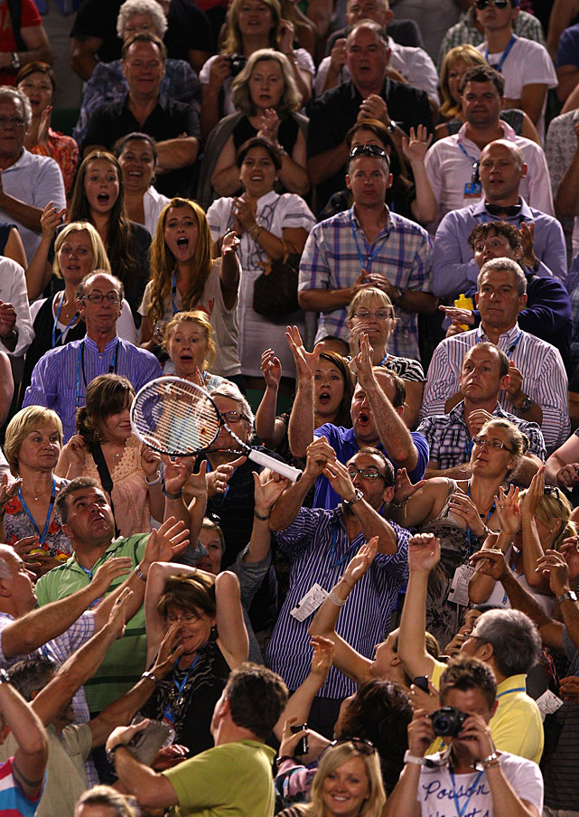 Members of the crowd catch the racket of Djokovic, who celebrated his victory by throwing it into the stands.