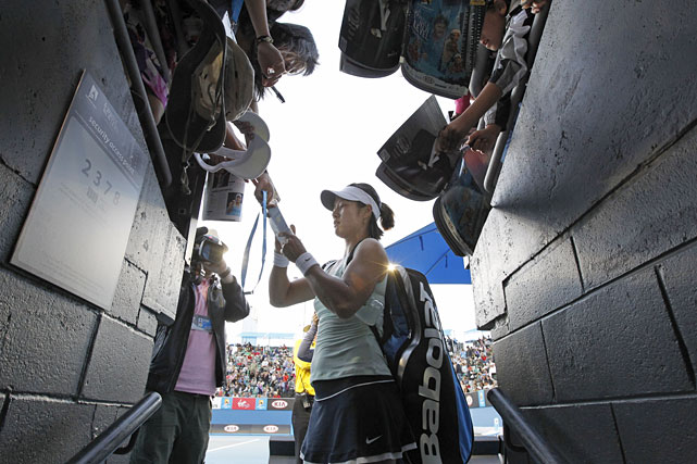 Li Na of China signs autographs for fans after beating Evgeniya Rodina of Russia.