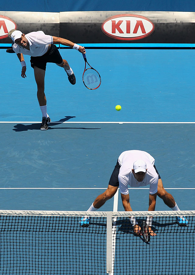 Daniel Nestor of Canada (top) serves during a third-round doubles match with Max Mirnyi of Belarus (bottom).