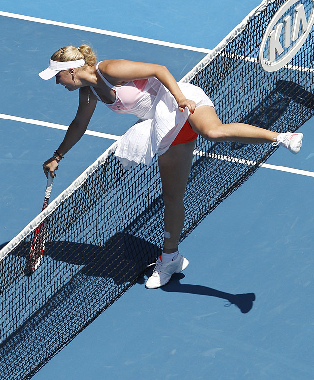 Wozniacki leans over the net and attempts to keep her balance after defeating Sevastova.