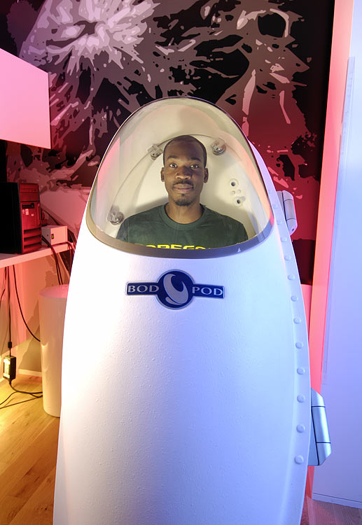 Professor James Harris, Oregon's assistant athletic director for student athlete development, sits in the Bod Pod, a machine that measures an athlete's fat-to-muscle ratio.