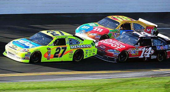 Menard gets a little push from Tony Stewart (14) as Kyle Busch (18) looks to pass. Busch placed eighth, with Menard ninth and Stewart 13th.