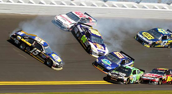 The cars of Michael Waltrip (15), Brian Keselowski (92), David Reutimann (00), Andy Lally (71), Joe Nemecheck (87), Greg Biffle (16) are tangled in an early-race crash as AJ Allmendinger (43) approaches.