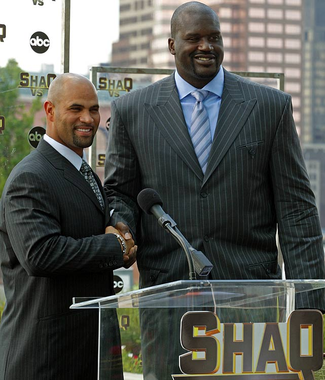 Pujols stands on a chair next to Shaquille O'Neal for a photograph at a press conference for ABC's  Shaq Vs.  at the Four Seasons Hotel in St. Louis.