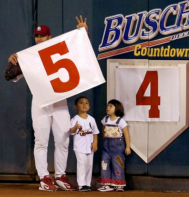 Pujols is joined by his son, Albert Jr., and daughter, Isabella, as he changes the number on the Busch Stadium Games Remaining sign.