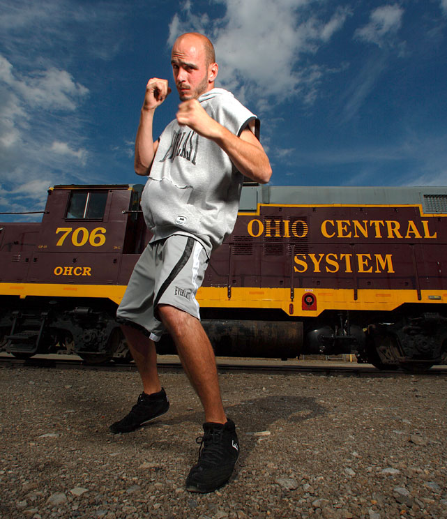 Pavlik poses in front of a locomotive train in Youngstown.