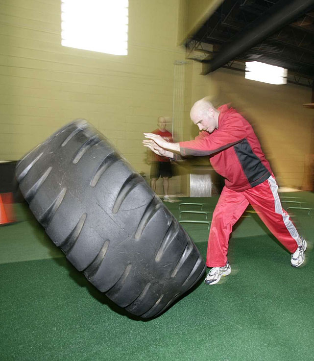 Pavlik demonstrates a tire tip drill during a workout at the Ironman Warehouse in Youngstown.