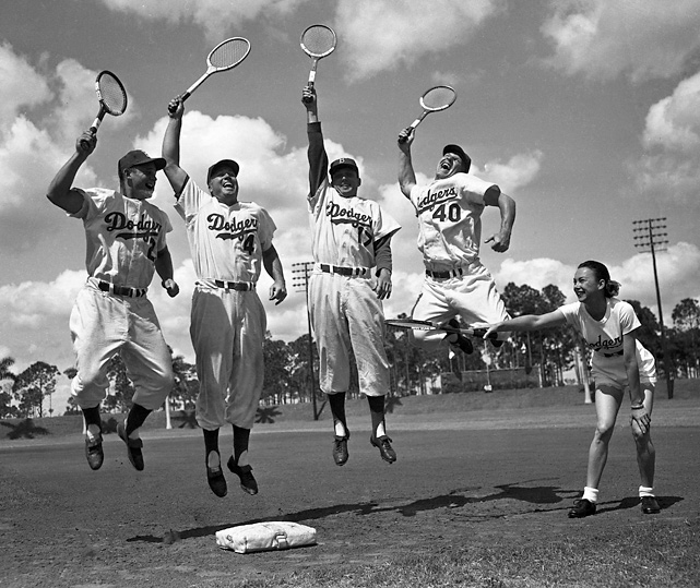 Snider and teammates Don Zimmer, Carl Erskine, and Walt Moryn take a break from spring training practice and work on their skills with tennis star Gussie Moran.
