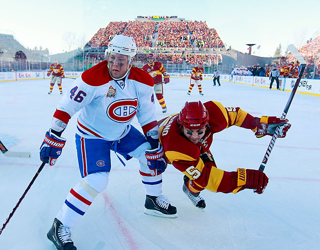 Montreal's Andrei Kostitsyn and Calgary's Mark Giordano battle near the boards.