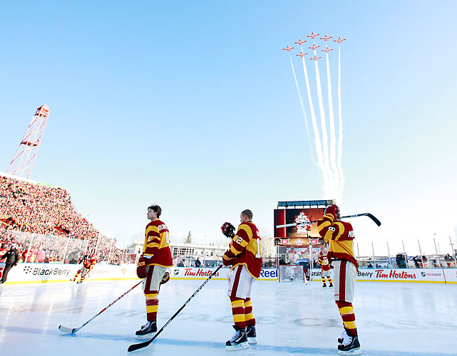 Jay Bouwmeester (left to right), Jarome Iginla and Brendan Morrison look on as the Canadian Snowbirds perform a flyover at the end of the national anthem.