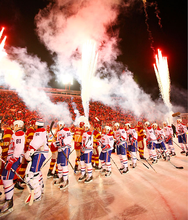 Players shake hands after the game as night falls on Calgary.