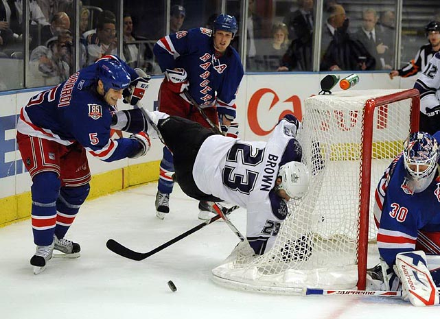 Rangers defenseman Dan Girardi knocks L.A. Kings forward Dustin Brown into the net during a game at Madison Square Garden.  Brown had goals in the first and third periods, but the Rangers won 4-3 after a shootout.