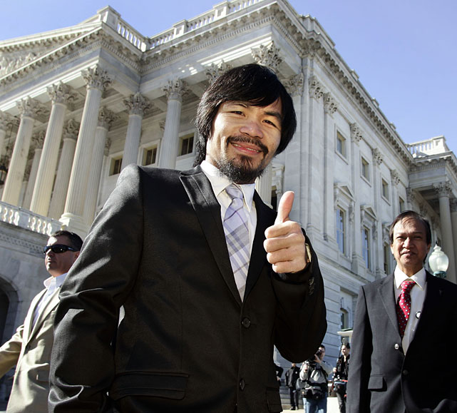 Eight-division world champion Manny Pacquiao visited Capitol Hill on Tuesday, where he was walked across the floor of the Senate by Nevada Sen. Harry Reid before meeting with the press. Pacquiao, who was elected to Congress in the Philippines in May, later met with President Barack Obama. The President gave Pacquiao three grocery bags full of light blue M&M's with the presidential seal, plus a watch adorned with the seal.