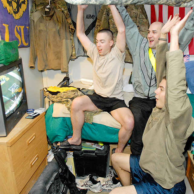Spc. Justin Webberly, Spc. Don Ellen, Pfc. Matthew Reynolds and Sgt. Cedric Allen of the 10th Mountain Division react to a touchdown as they watch the first half from Kandahar Airfield in Kandahar, Afghanistan.