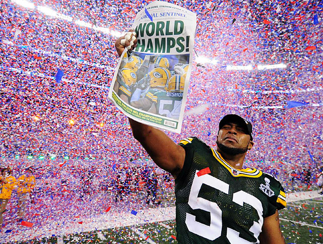 Packers linebacker Diyral Biggs holds up a newspaper celebrating the Packers' first Super Bowl title since the 1996-97.