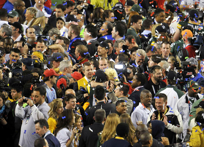 A cluster of media swarms the field following the Packers' win.