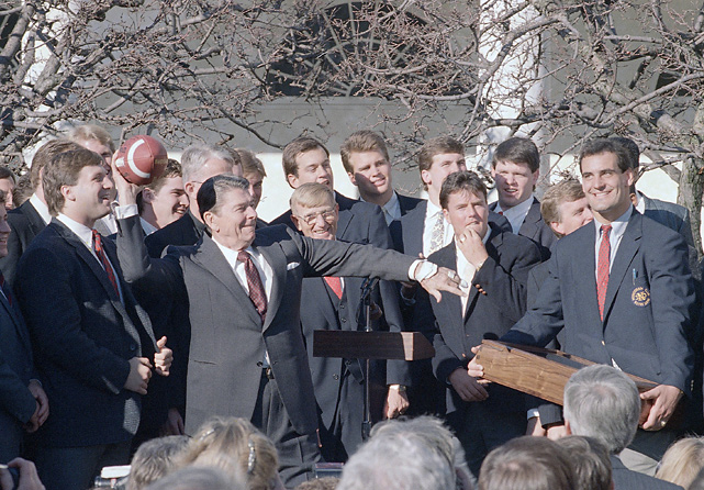 President Reagan rears back to pass a football presented him by the Notre Dame football team during a ceremony in the Rose Garden. Behind Reagan is the Irish head coach Lou Holtz.